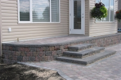 Rustic Pisa 2 block retainer wall steps from patio to raised pad