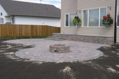 Rustic Roman Euro patio with charcoal border and fire pit with circle patio